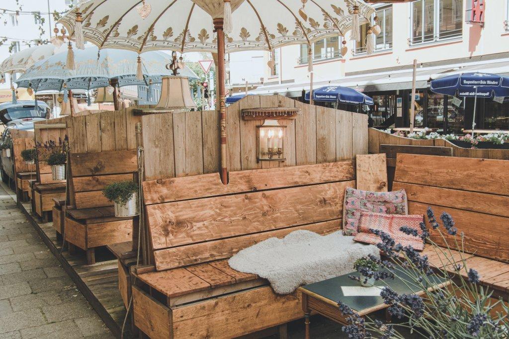 Entspannte Sitzflächen mit blumigen Freu(n)den und flauschigen Kissen – Café Lozzi sorgt für Gemütlichkeit. – ©wunderland media GmbH