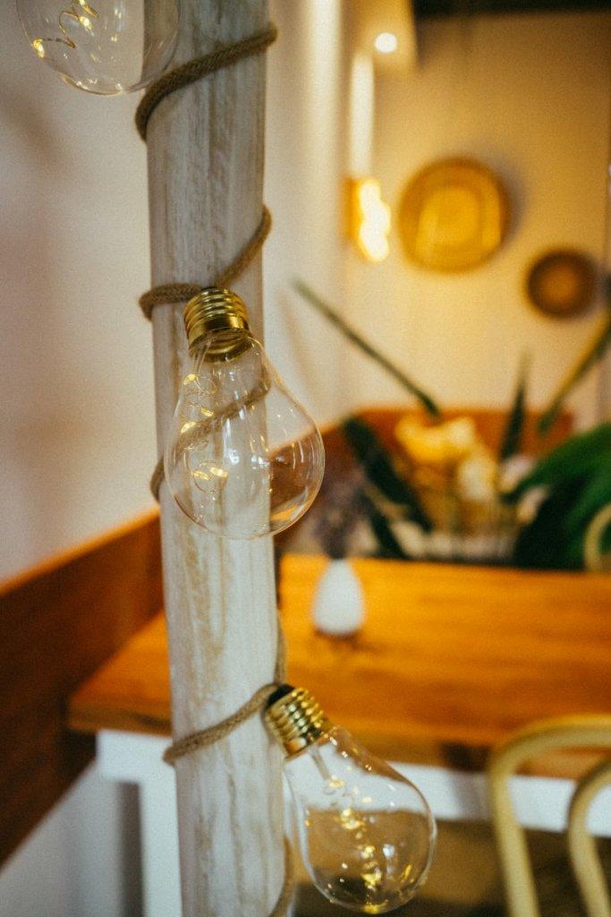 Glühbirnen, die an einem Stamm befestigt sind im Café Palmtree Club. Im Hintergrund ist die Boho Einrichtung zu erkennen. – ©Ben Sagmeister für wunderland media GmbH