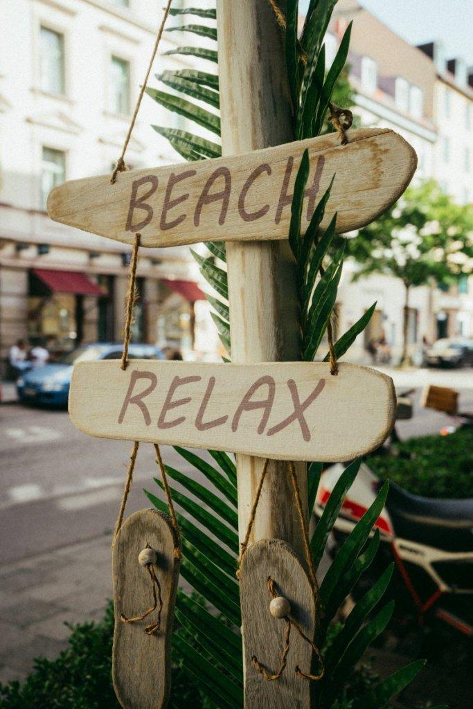 Ein Wegweiser aus Holz mit den Beschriftungen Beach und Relax vor dem Café Palmtree Club – ©Ben Sagmeister für wunderland media GmbH
