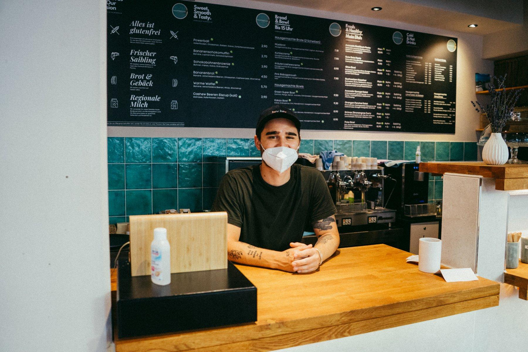 Ein junger Mann mit Maske steht hinter der Holztheke des Café Palmtree Club – ©Ben Sagmeister für wunderland media GmbH