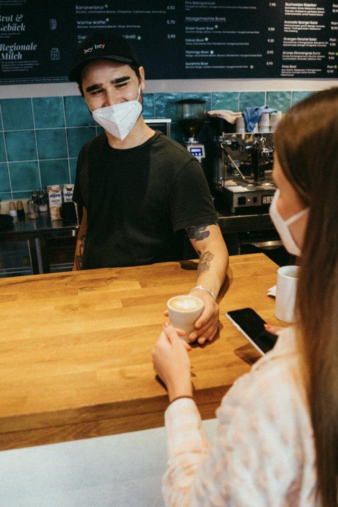 Inhaber Benni überreicht einer Kundin einen Cappuccino im Café Palmtree Club – ©Ben Sagmeister für wunderland media GmbH