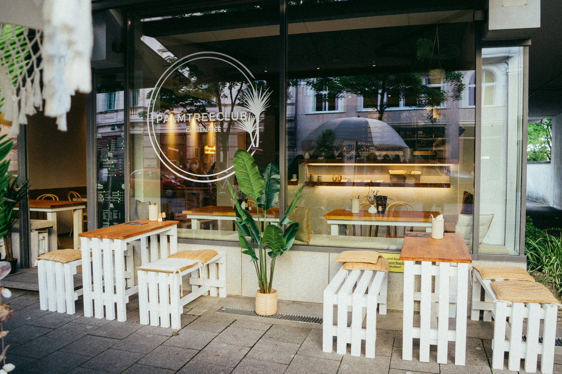 Holztische und Bänke vor dem Palmtree Club in München – ©Ben Sagmeister für wunderland media GmbH
