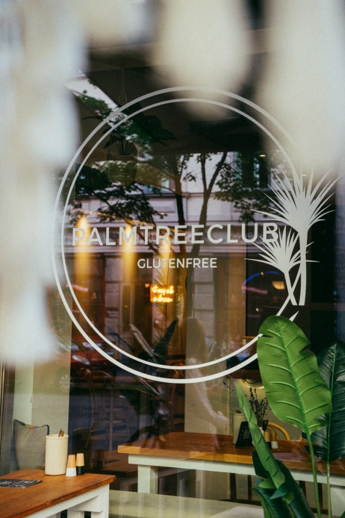 Ein Klebeschild mit der Aufschrift Palmtree Club auf einer Glasscheibe eines Cafés – ©Ben Sagmeister für wunderland media GmbH